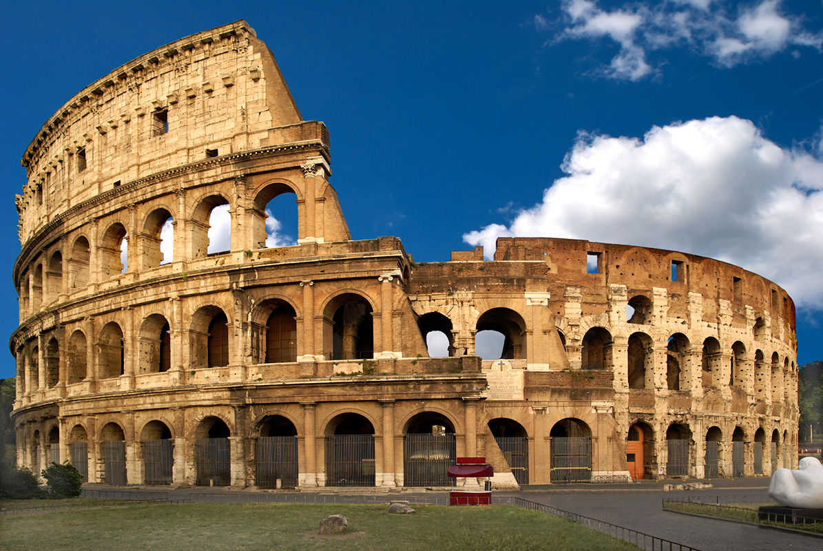 The famous Colosseum in Rome on a sunny day. Free of tourists. Blue sky, some nice clouds.